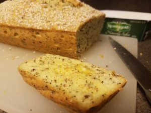 keto seeded bread loaf, slice with butter and garlic salt