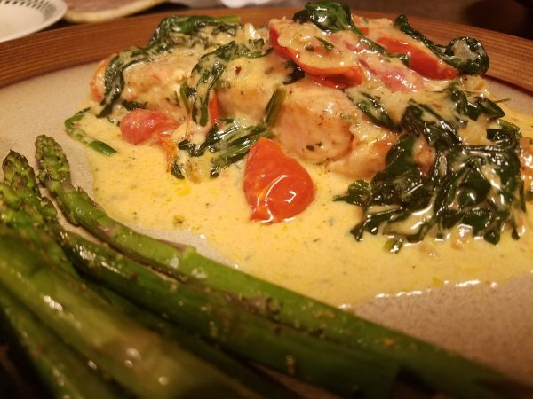 KETO Salmon with creamy buttery tomato garlic spinach sauce, side of asparagus. Low-carb.